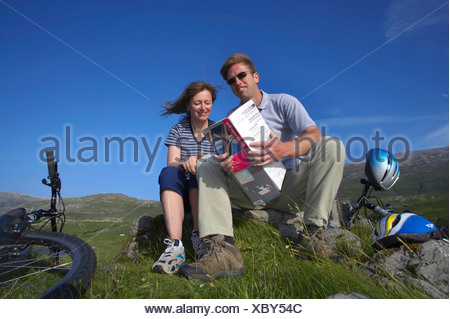 young couple taking a break during a cycle ride through the highlands, United Kingdom, Scotland, Sutherland, Loch Assynt - Stock Photo