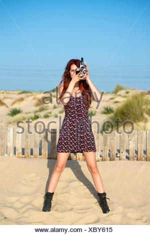 Spain, El Puerto de Santa Maria, young woman using old film camera on the beach - Stock Photo