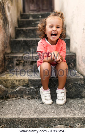 Portrait of laughing little girl sitting on steps - Stock Photo