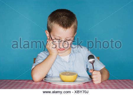 Sullen boy with grapefruit - Stock Photo