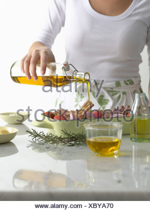 Woman pouring olive oil over roast dish - Stock Photo