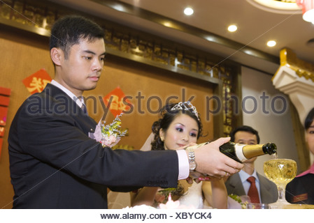 Bride and groom pouring champagne together at reception - Stock Photo