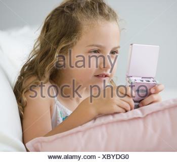 Girl playing handheld video game - Stock Photo