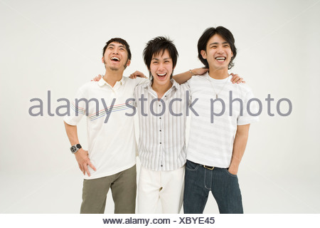 Three young men standing with arms around - Stock Photo