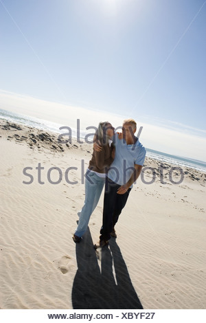 Senior couple embracing on beach - Stock Photo