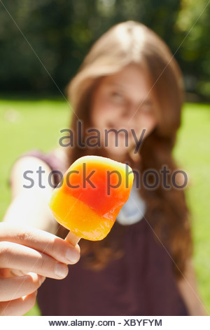 Young girl eating a popsicle in a park - Stock Photo