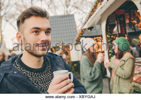 Man having a hot punch on the Christmas Market - Stock Photo