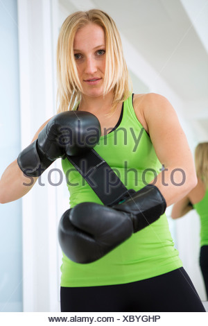 Boxer putting on boxing gloves in gym - Stock Photo