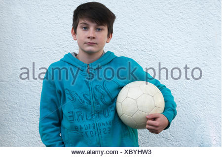 Boy, 10 years, holding a football under his arm, standing in front of a white wall, Baden-Württemberg, Germany - Stock Photo