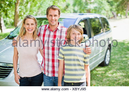 Family smiling together by car - Stock Photo