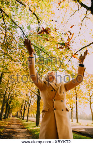 Woman throwing autum leaves in the air - Stock Photo