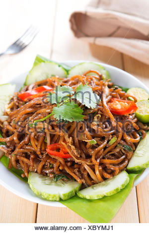 Asian style spicy fried noodles, ready to serve on dining table. - Stock Photo