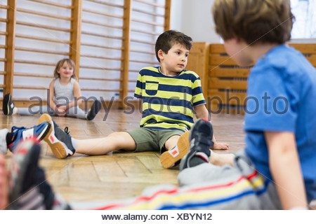 Children sitting on wooden floor, legs apart - Stock Photo