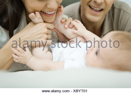 Parents smiling down at baby, mother holding baby's feet, cropped view - Stock Photo