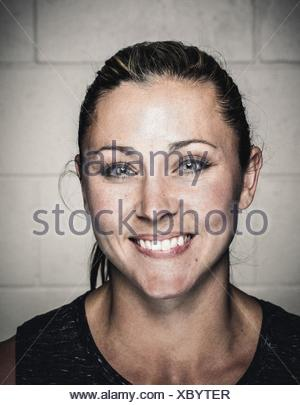 Portrait of confident young woman before workout - Stock Photo