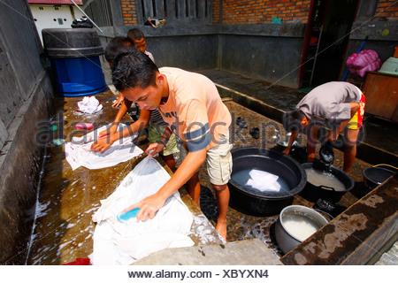 Children washing school uniforms, Margaritha children's home, Marihat, Batak region, Sumatra island, Indonesia, Asia - Stock Photo