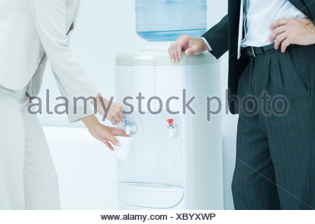 Professional woman filling disposable cup with water from water cooler, male colleague standing nearby, cropped view - Stock Photo