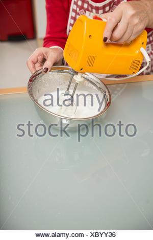 Senior woman mixing meringue in mixing bowl in kitchen, Munich, Bavaria, Germany - Stock Photo