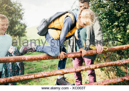 Girl climbing over wooden fence - Stock Photo