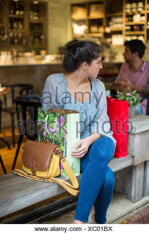 Young woman shopper sitting outside cafe looking over her shoulder - Stock Photo
