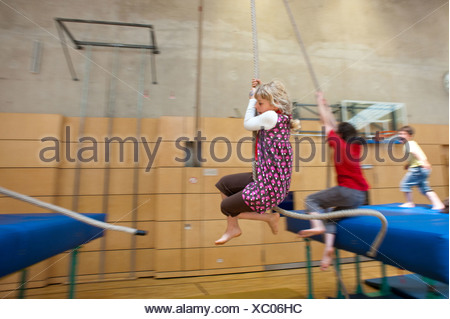 Berlin, Germany, blond girl swinging on a rope in a gymnasium - Stock Photo