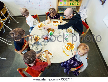 High angle view of kindergarten students and teacher having food at dining table - Stock Photo