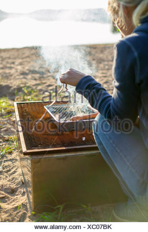 Sweden, Vastergotland, Lerum, Woman cooking by lake - Stock Photo