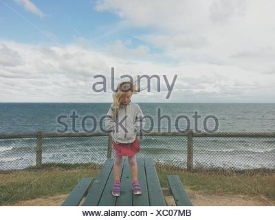 Girl standing on a picnic table by the sea - Stock Photo