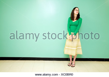 Young woman against a green wall - Stock Photo