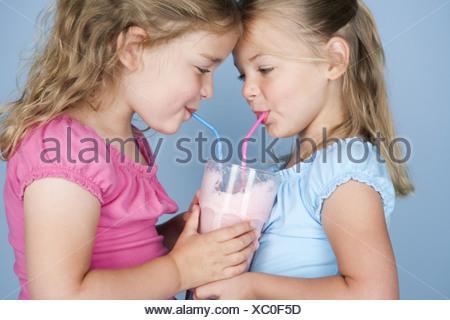 Two girls sharing a milkshake - Stock Photo