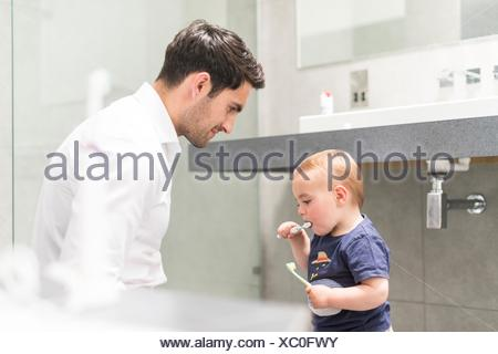 Father watching young brush teeth - Stock Photo