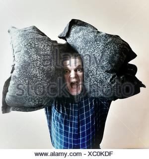 Portrait Of Man Screaming While Carrying Pillows Against White Background - Stock Photo