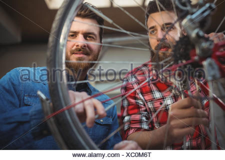 Low angle view of two mechanics repairing a bicycle wheel - Stock Photo