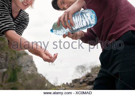 Man pouring water onto womans hands - Stock Photo