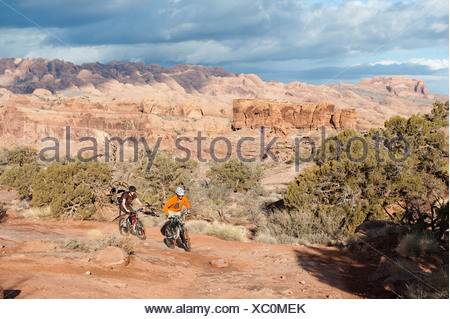 Two young men ride their bikes across the slickrock on the Amasa Back Trail in Moab, UT. - Stock Photo