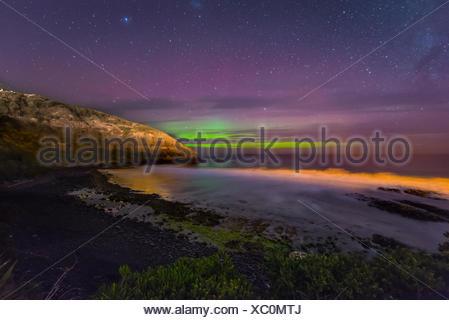 Southern lights, aurora australis over the sea, sand dunes, Second Beach, Dunedin, Otago, Southland, New Zealand - Stock Photo