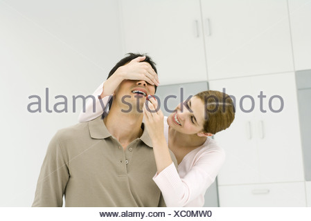 Woman covering man's eyes with her hand, feeding him a fresh strawberry - Stock Photo