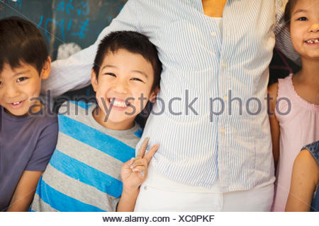 A group of children in school with their teacher. - Stock Photo