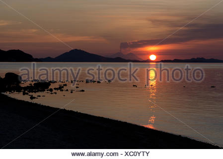 View of coastline with erupting volcano in distance at sunset, Sangeang Api (Mount Sangeang), Kelor Island, near Flores Island, - Stock Photo