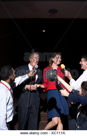 A politician and his wife being interviewed by reporters - Stock Photo