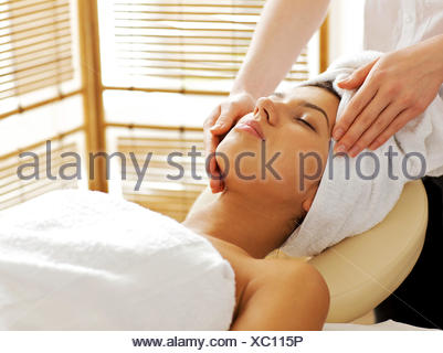 Young woman receiving facial massage, eyes closed - Stock Photo