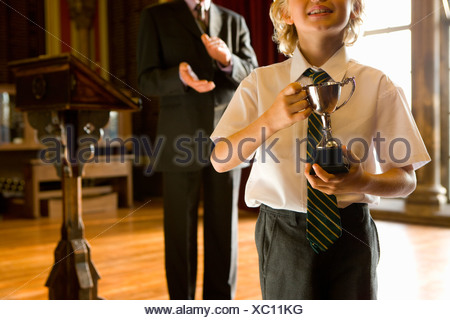 Boy (5-7) with trophy, man clapping by lectern in background, mid section - Stock Photo