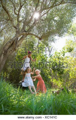 Three girls playing on tree tire swing in garden - Stock Photo