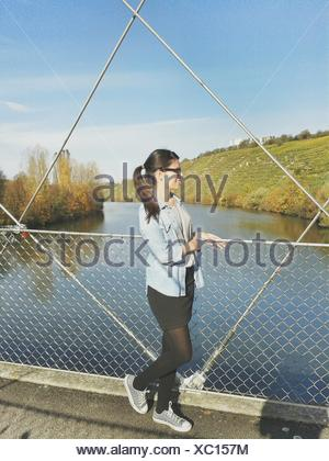 Full Length Of Woman Standing On Pedestrian Walkway Over River Against Sky - Stock Photo