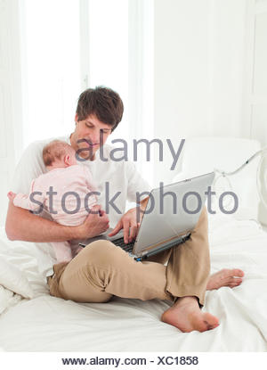 Father holding baby and using laptop - Stock Photo