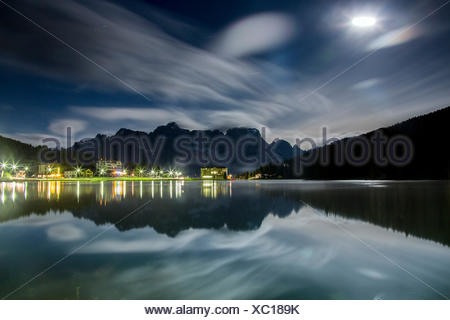 Clouds illuminated by the moon are reflected in Lake Misurina, Cortina d'Ampezzo, Dolomites, Veneto, Italy, Europe - Stock Photo