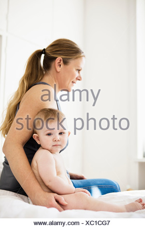 Mother sitting with baby girl on bed - Stock Photo