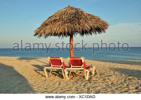 Empty sunbeds under a parasol on the beach of Playa Ancón near Trinidad, Cuba, Caribbean - Stock Photo