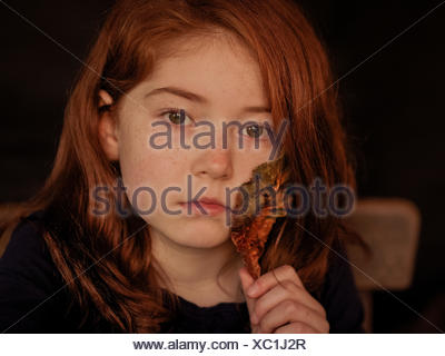 Portrait of girl holding autumn leaf - Stock Photo