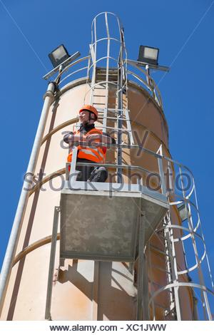 Worker looking out from smoke stack viewing platform - Stock Photo